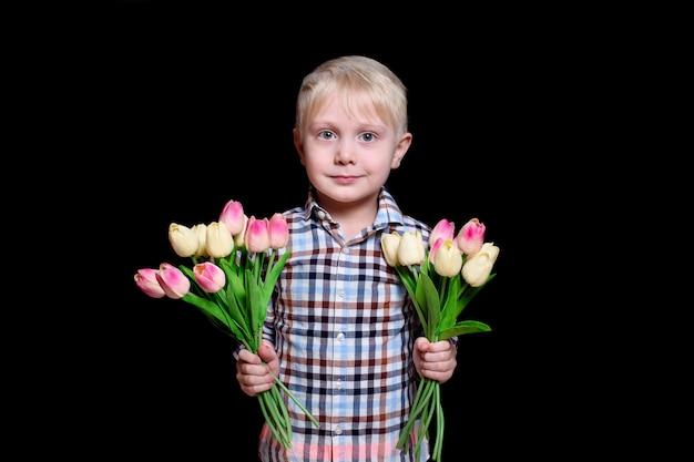 Netter blonder junge des porträts mit zwei blumensträußen von tulpen. muttertag-konzept Premium Fotos