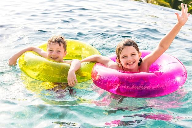 Netter bruder und schwester, die im pool schwimmt Premium Fotos