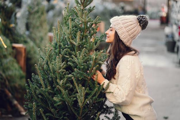 Netter brunette in einer weißen strickjacke mit weihnachtsbaum Kostenlose Fotos