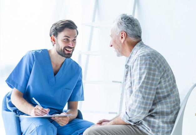 Netter doktor, der mit älterem patienten spricht Kostenlose Fotos