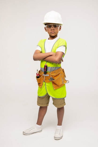 Netter ernsthafter kleiner reparaturmann in freizeitkleidung, helm, schutzbrille und uniformjacke, die seine arme mit der brust verschränkt Premium Fotos