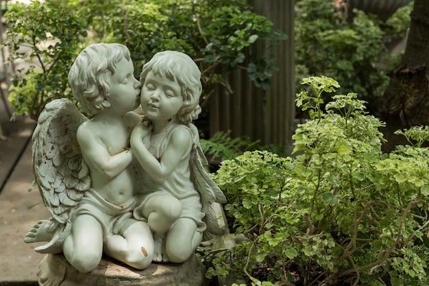 Netter geküsster paar-amor im garten Premium Fotos