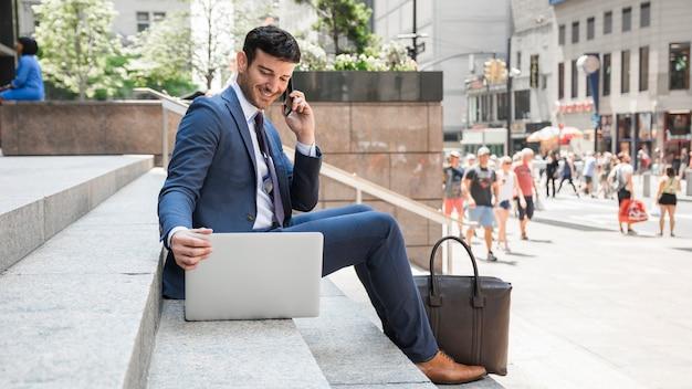 Netter geschäftsmann, der am telefon spricht und laptop verwendet Kostenlose Fotos
