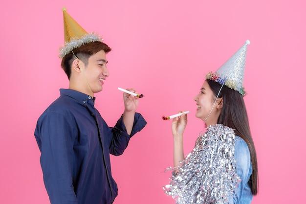 Netter jugendlichmann des porträts und hübsche frau mit parteistütze, tragen sie partyhut und das spielerische genießen auf rosa Kostenlose Fotos
