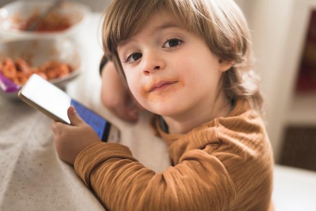 Netter junge, der bei tisch telefon hält Kostenlose Fotos