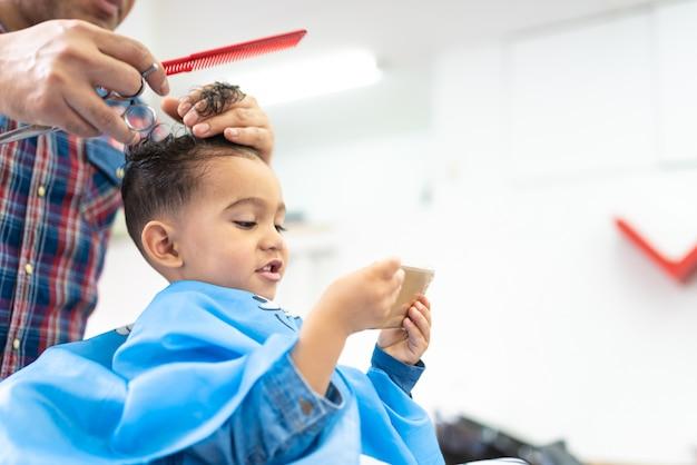 Netter junge, der ein haar geschnitten in einen friseur shop beauty concept erhält Premium Fotos