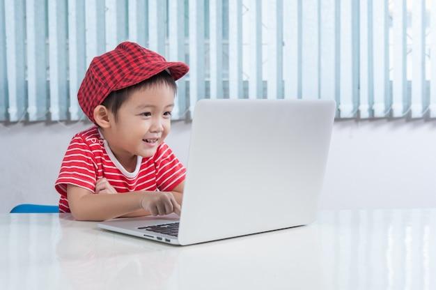 Netter junge, der labtop im kinderzimmer spielt Kostenlose Fotos