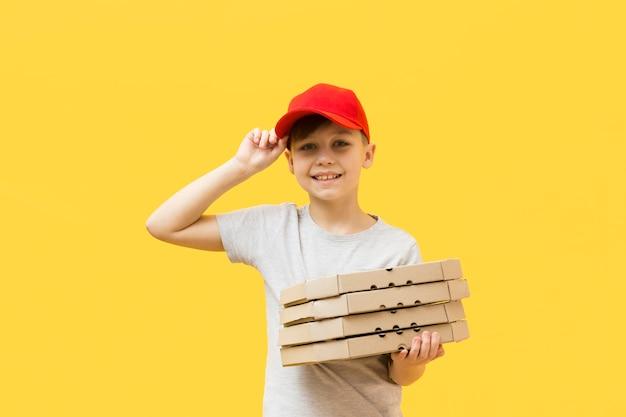 Netter junge, der pizzaschachteln hält Kostenlose Fotos