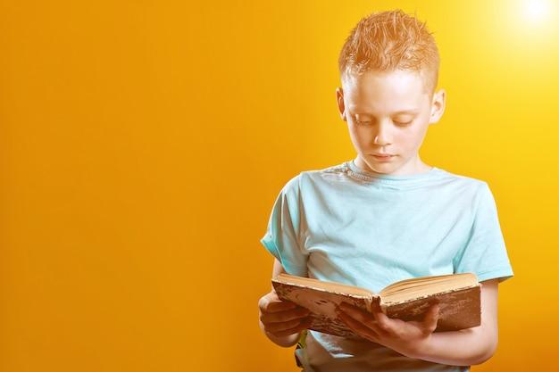 Netter junge in einem hellen t-shirt, das ein buch auf gefärbt hält Premium Fotos