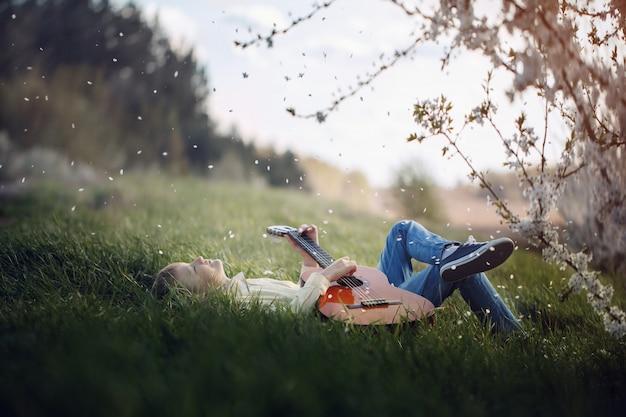 Netter junge liegt auf dem gras mit einer gitarre auf sonnenuntergang Premium Fotos