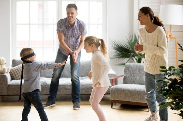 Netter junge mit verbundenen augen, der versteckenspiel mit familie spielt Kostenlose Fotos