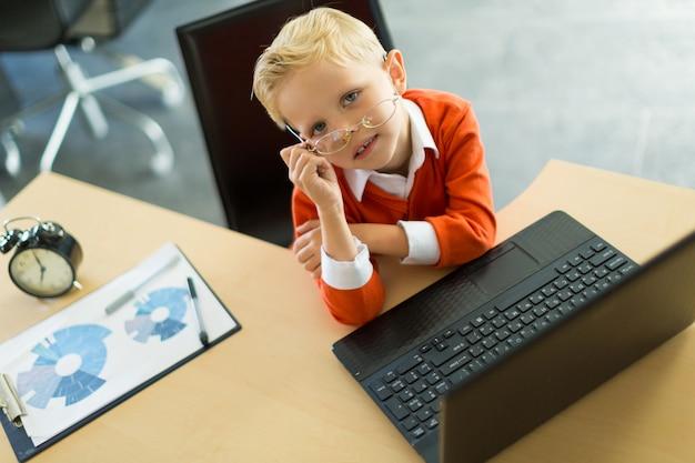 Netter junge sitzen am schreibtisch im büro und benutzen computer Premium Fotos