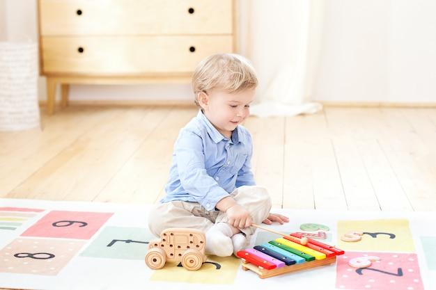 Netter junge spielt mit einem bunten musikinstrument des xylophons. lernspielzeug für kleine kinder. das konzept der kindheit und der kindlichen entwicklung. kind zu hause im kinderzimmer. Premium Fotos