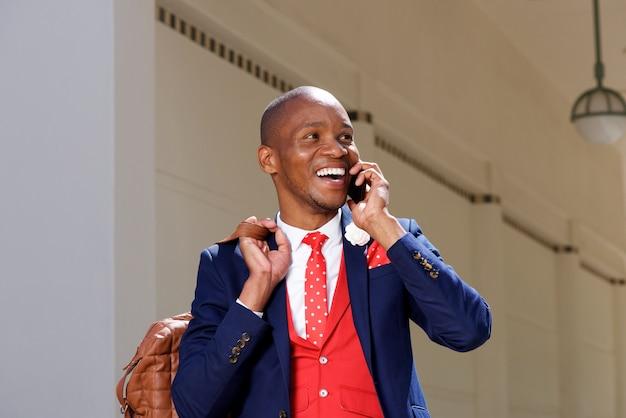 Netter junger afrikanischer mann in der klage sprechend am handy Premium Fotos