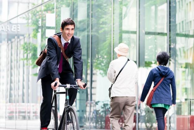 Netter junger angestellter, der gebrauchsrad in berlin fährt Premium Fotos