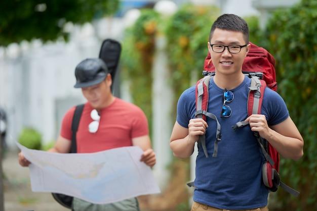 Netter junger asiatischer mann, der mit rucksack und dem freund betrachtet karte aufwirft Kostenlose Fotos