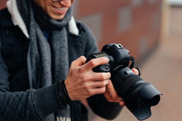 Netter junger mann betrachtet fotos in der kamera. gekleidete, warme jacke, grauer schal Kostenlose Fotos
