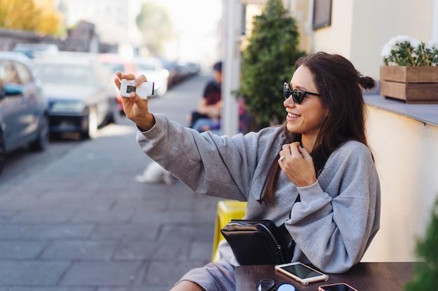 Netter, junger weiblicher blogger, der auf kamera aufwirft. Kostenlose Fotos