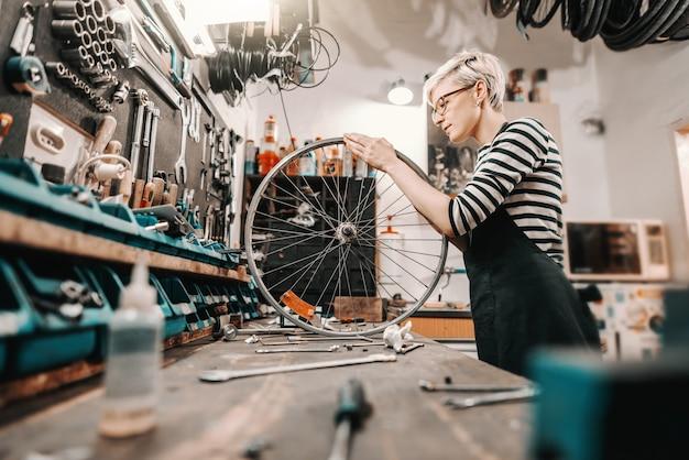 Netter kaukasischer weiblicher arbeiter, der fahrradrad hält und repariert, während er in fahrradwerkstatt steht. Premium Fotos