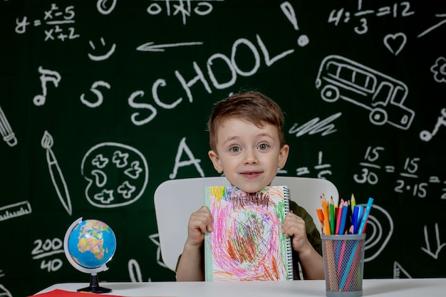 Netter kinderjunge, der hausaufgaben macht. cleveres kind, das am schreibtisch zeichnet. schüler. grundschüler zeichnen am arbeitsplatz. kind lernt gerne. heimunterricht. zurück zur schule. kleiner junge im schulunterricht Premium Fotos