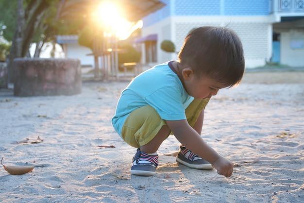 Netter kleiner asiatischer junge, der sand am park spielt Premium Fotos