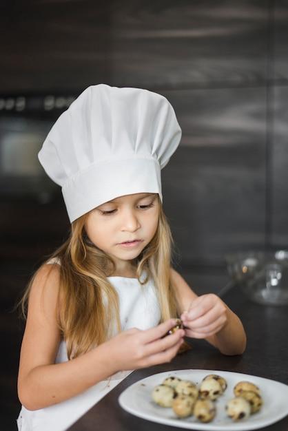Netter kleiner chef, der wachtelei in der küche pisst Kostenlose Fotos