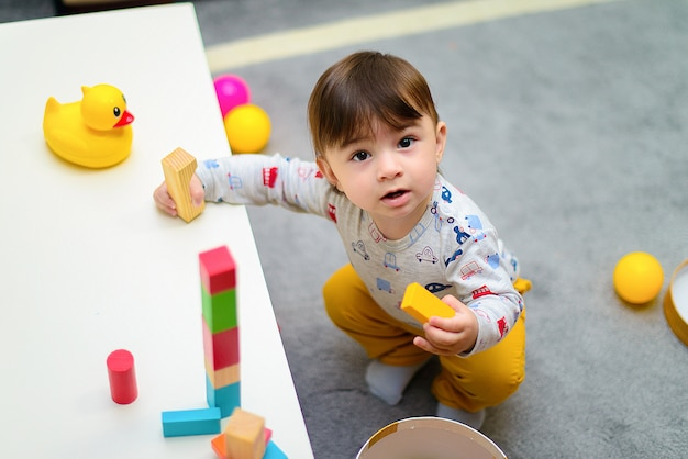 Netter kleiner genießender junge beim spielen mit spielwaren oder blöcken an seinem raum Premium Fotos