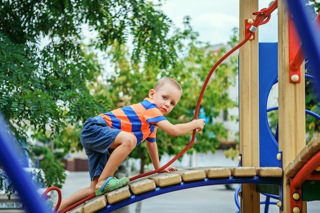 Netter kleiner junge, der auf dem spielplatz im sommer in der stadt spielt Premium Fotos