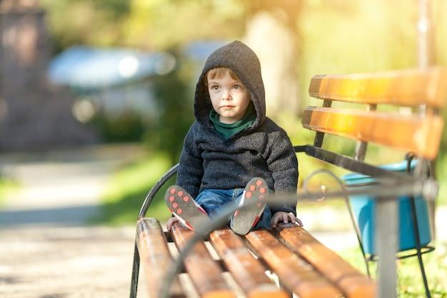 Netter kleiner junge, der auf einer bank sitzt Kostenlose Fotos