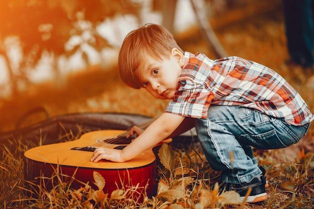 Netter kleiner junge, der in einem park spielt Kostenlose Fotos