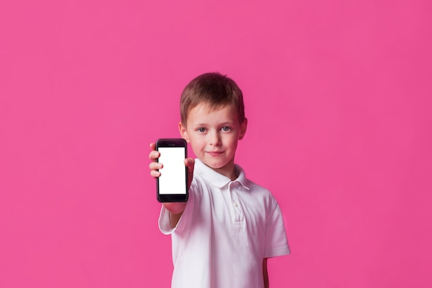 Netter kleiner junge, der mobiltelefon des leeren bildschirms auf rosa hintergrund zeigt Kostenlose Fotos