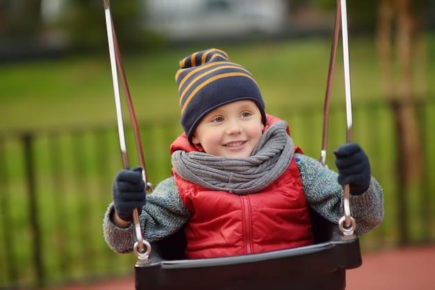 Netter kleiner junge, der spaß auf spielplatz im freien hat. kind auf schaukel Premium Fotos