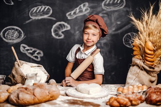Netter kleiner junge mit dem chefhutkochen Premium Fotos