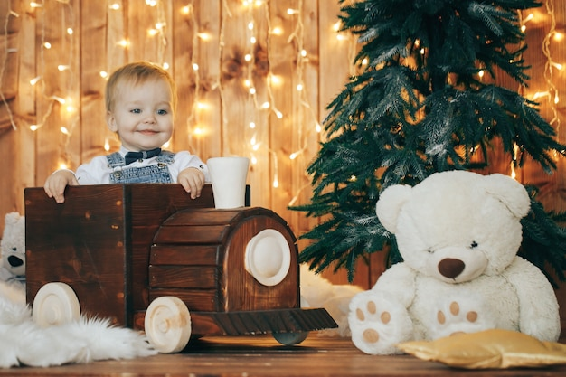 Netter kleiner junge mit weihnachtslichtern und dekorationen Premium Fotos