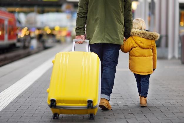 Netter kleiner junge und sein vater, die eilzug auf bahnhofsplattform wartet Premium Fotos