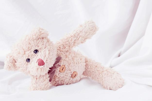Netter kleiner teddybär legte sich auf das bett. Premium Fotos