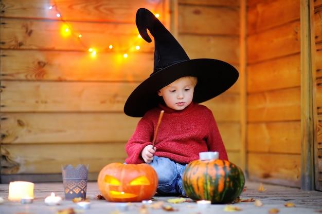 Netter kleiner zauberer, der mit halloween-kürbisen mit lichtern spielt Premium Fotos