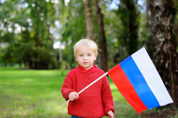 Netter kleinkindjunge, der draußen russische flagge hält Premium Fotos