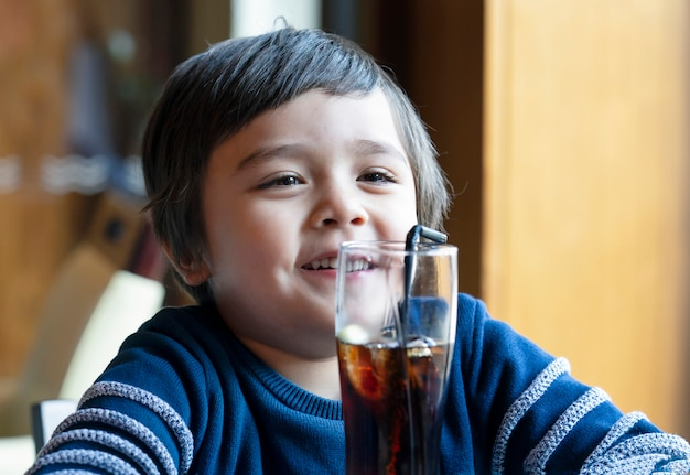 Netter kleinkindjunge, der kaltes getränk trinkt Premium Fotos
