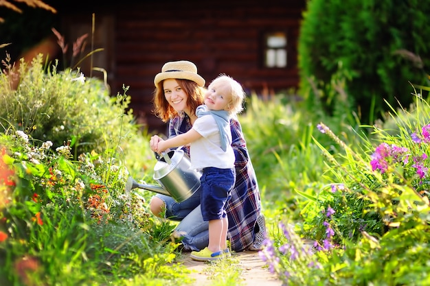 Netter kleinkindjunge und seine bewässerungsanlagen der jungen mutter im garten am sonnigen tag des sommers Premium Fotos