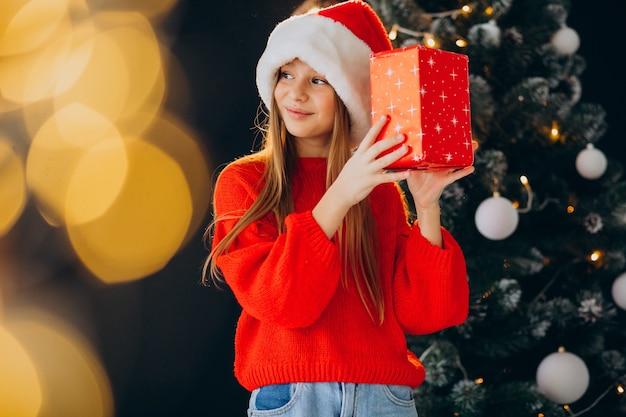 Netter mädchenjugendlicher im roten weihnachtsmannhut durch weihnachtsbaum Kostenlose Fotos