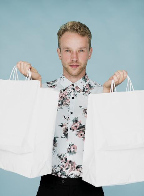 Netter mann mit den einkaufstaschen, die zur kamera schauen Kostenlose Fotos