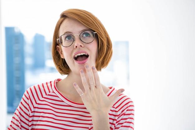 Netter roter behaarter hippie mit gläsern vor einem fenster Premium Fotos