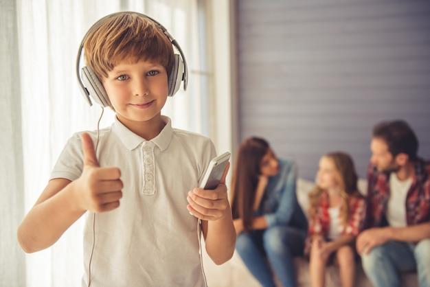 Netter schuljunge in den kopfhörern hört musik. Premium Fotos