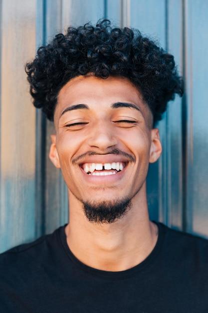 Netter schwarzer junger mann mit dem lockigen haar Kostenlose Fotos
