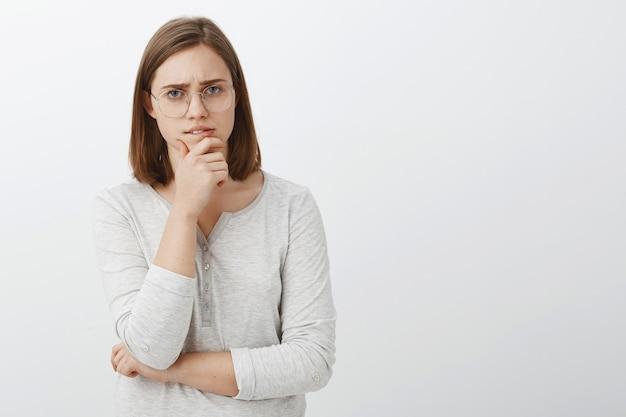 Netter weiblicher geek, der versucht, hartes mathe-rätsel zu lösen, das nachdenklich über weißer wand steht, die kinn reibt, während brainstorming schaut, während entscheidung trifft oder über graue wand posiert Kostenlose Fotos