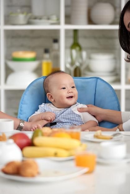 Nettes asiatisches baby an speisetische mit familie Kostenlose Fotos