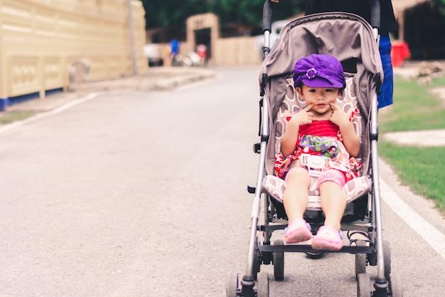 Nettes asiatisches baby, das auf kinderwagenwagen sitzt und das lächeln aufwirft Premium Fotos