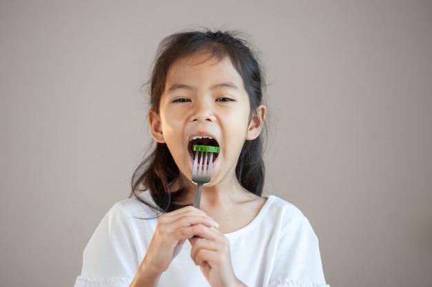 Nettes asiatisches kindermädchen, das gesundes gemüse mit gabel isst Premium Fotos
