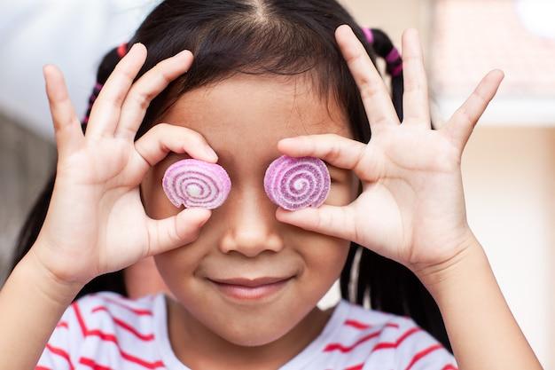 Nettes asiatisches kindermädchen mit geleesüßigkeiten lächelnd und ein lustiges gesicht machend Premium Fotos